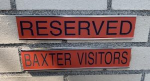 Reddish-Orange Sign on wall says Reserved Baxter Visitors